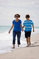 Woman with her grandson walking on the beach