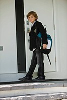 Portrait of a schoolboy opening the door of a school