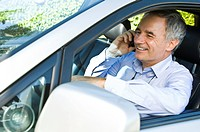 Man sitting in a car and talking on a mobile phone