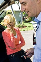 Man holding a car key beside a woman talking on a mobile phone