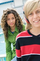 Teenage boy listening to music with headphones and a girl sitting behind him