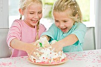 Two girls playfully inserting their hands in a birthday cake