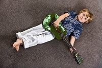 Boy lying on a round table and playing a guitar