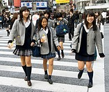 Three young Japanese schoolgirls crossing street at Shibuya in central Tokyo Japan