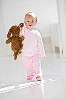 Baby girl walking on the floor with a toy