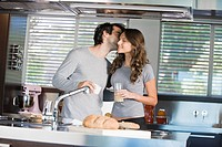 Man kissing a woman in the kitchen