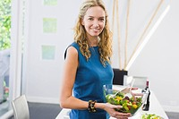 Woman holding a bowl of salad and smiling