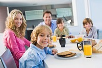 Portrait of a family having breakfast and smiling