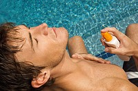 Man applying suntan lotion on his body at the poolside