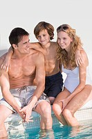 Family sitting at the poolside and smiling (thumbnail)