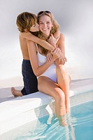 Boy hugging his mother at the poolside and smiling (thumbnail)