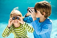 Two boys looking through binoculars