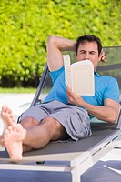 Man reading a book on a lounge chair (thumbnail)