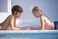 Boy with a girl playing at the poolside