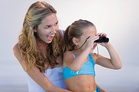 Girl looking through binoculars with her mother laughing