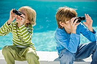 Two boys looking through binoculars at the poolside