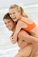 Man giving woman piggyback ride on the beach (thumbnail)