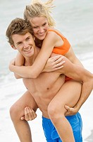 Man giving woman piggyback ride on the beach