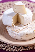 Wedge of fresh creamy cheese with seasoned form underneath