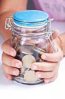 Child's hands holding a jar filled with cents