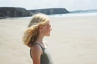 Blonde girl standing on the beach, looking at the sea, Bretagne, France, Europe