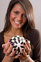 Young brunette woman holding black and white ball