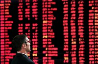 Stockbroker in front of a screen showing market prices in a stock exchange