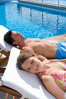 Couple laying on lounge chairs with eyes closed at poolside