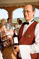 Waiter holding wine bottle with well_dressed couples dining in background