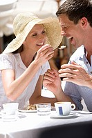Woman feeding man dessert at sunny, outdoor cafŽ