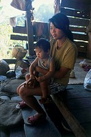 Photograph of a Thai mother and her son in a small hut