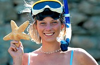 smiling woman holding seastar, wearing snorkling equipment