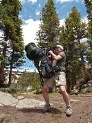 John West, 62, lifting a heavy pack while backpacking in the Missouri Lakes area of the Holy Cross Wilderness, White River National Forest, Colorado, ...