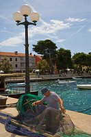 Fisherman fixing net, Harbour of Fazana, Istria, Croatia, Europe