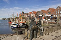 Shrimp boats in the harbor of Neuharlingersiel, in front the bronze sculpture Altfischer und Jungfischer, Old Fisherman and Young Fisherman, Nationalp...