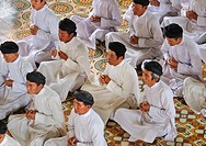 Praying devout men, ceremonial midday prayer in the Cao Dai temple, Tay Ninh, Vietnam, Asia