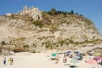 Colourful sun umbrellas and people on a beach, church on cliff in the back, Tropea, Calabria, South Italy, Europe