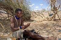 Member of the Hadzabe tribe making a hunting arrow, Lake Eyasi, Tanzania, Africa