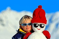 boy with snow man, wearing sun glasses, head to head