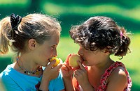 two girls eating fruits, looking at each other