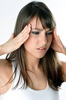 brunette woman with headache touching her temples.