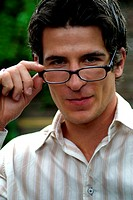 Portrait of a young man, placing one hand on his spectacles