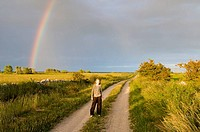 Girl standing in front of a rainbow. Öland, Sweden