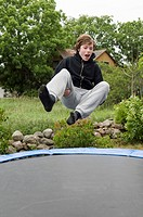 Boy jumping high on a trampolin