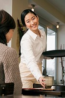 young japanese waitress serving guest at restaurant
