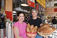 Detroit, Michigan - Jackie Victor in pink and Ann Perrault, owners of Avalon International Breads, hold some of their products inside their bakery