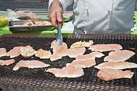 Livonia, Michigan - A caterer prepares chicken on an outdoor grill