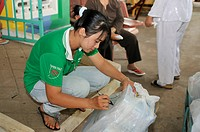 Sales clerk labelling a pack of fish sauce Nuoc Mam, Phu Quoc, Vietnam, Asia