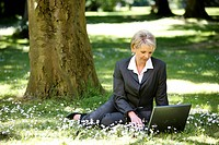 Woman wearing a ladies' suit, trouser suit, businesswoman, early 40s, working on her laptop in a park