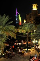 Open-air restaurant at the Madinat Jumeirah resort in front of the illuminated facade of the seven-star hotel Burj al Arab, Arabian Tower, Dubai, Unit...